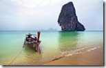 Fishing boat tied on a beach near limestone cliff, Railay Beach near Krabi, Thailand