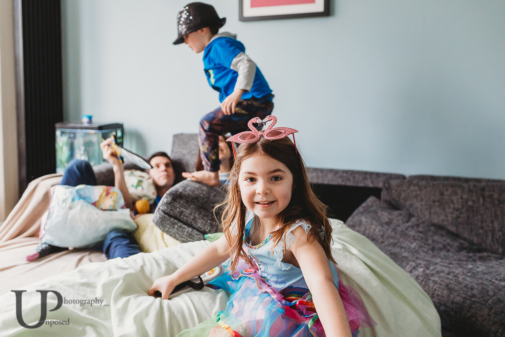 A young girl camera aware whilst a young boy dressed as The Greatest Showman jumps on a sofa in the background.