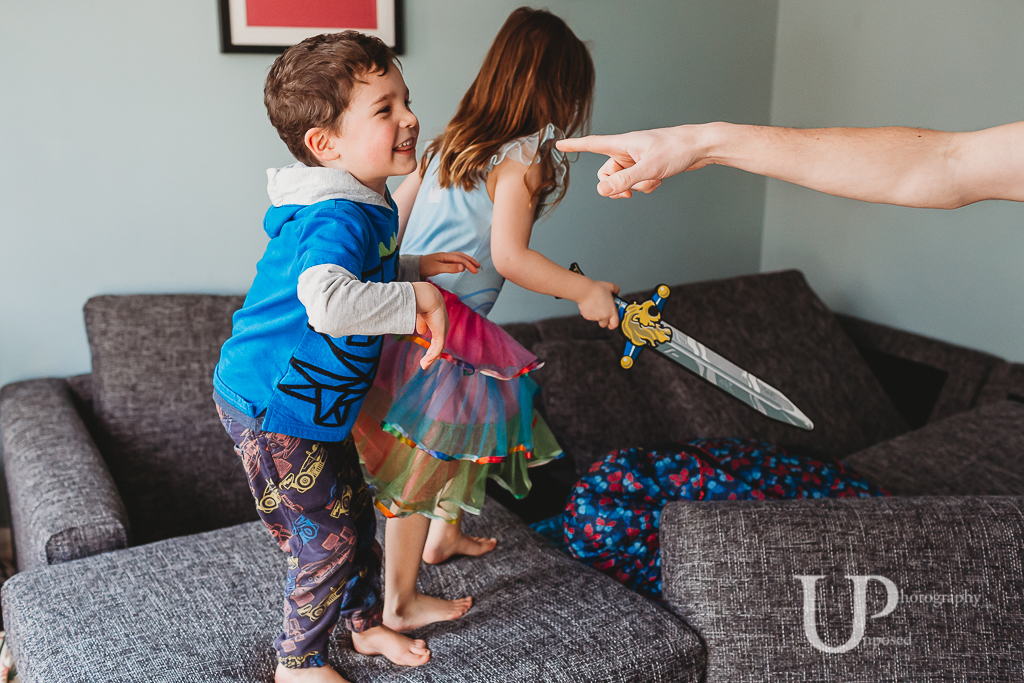 A young boy talking to his father while a young girl is running over the sofa with a play sword.