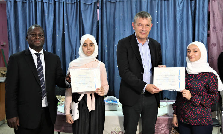 UNRWA Commissioner-General Philippe Lazzarini (2 from right) hands out certificates of appreciation for high academic achievement to two UNRWA students during his visit to the Damascus Training Center, accompanied by the Director of UNRWA Affairs in Syria, Michael-Ebye Amanya (left). © 2021 UNRWA Photo
