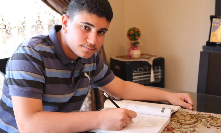 Ismail Ajjawi, photographed in his home near El Buss refugee camp, Lebanon. He achieved a top eight score in the Official Lebanese Baccalaureate (IB) examination across Lebanon and ranked number one for the whole south region. © 2019 UNRWA Photo by Abeer Nouf.