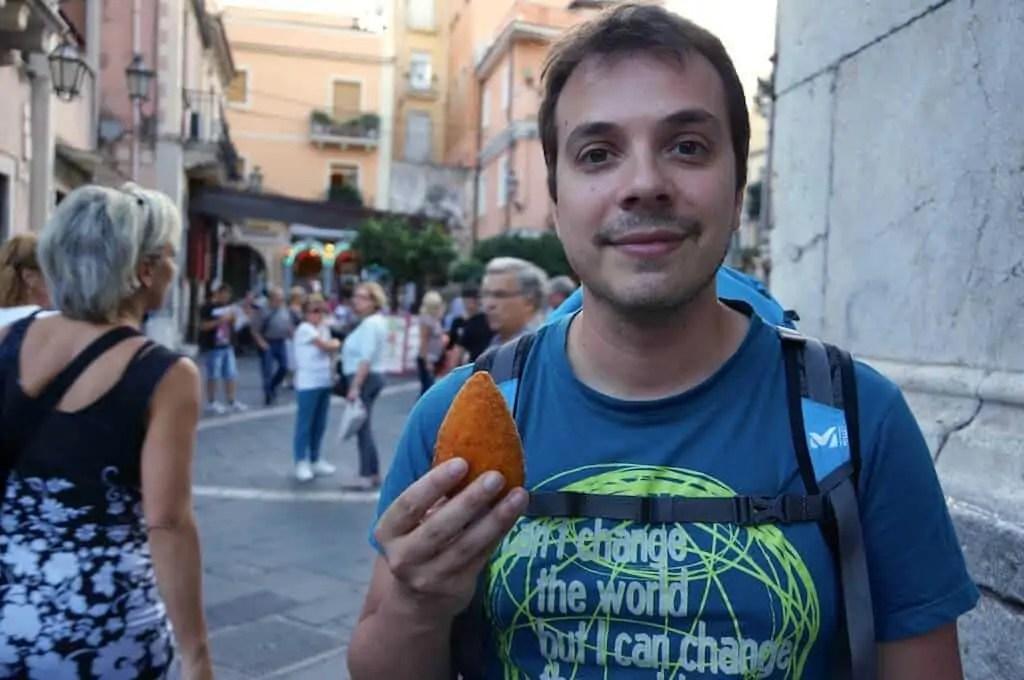 François et un arancino, dans la grand rue de Taormina