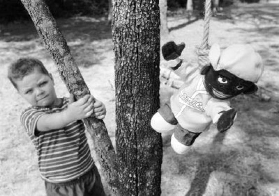Dustin Jones, 5, son of David and Kristy Jones of Laurel, Mississippi, is pictured with a doll hanging at the home of South Mississippi Knights of the Ku Klux Klan Imperial Wizard Jimmie Maxey during a memorial rally on August 10, 2002, in Petal, Mississippi, following Maxey's death. (PHOTO BY JAMES EDWARD BATES)