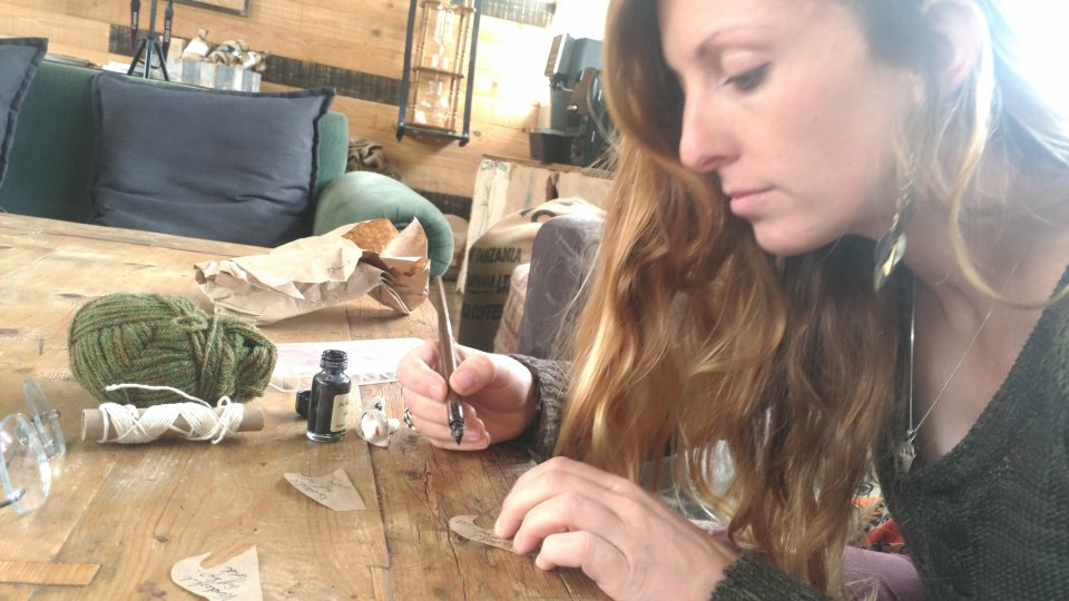 Vikki working at a craft table, writing hand-made labels