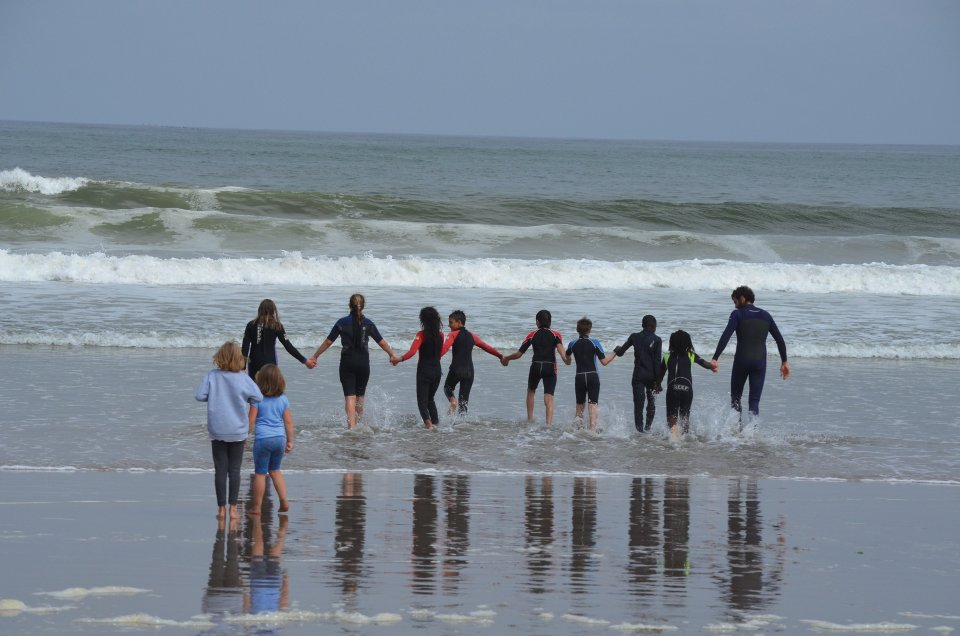 A group of children wearing wetsuits, holding hands, and walking in a line into the ocean with Fransesco at one end