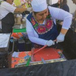 Woman at Oaxacan Kitchen Markets pressing tortillas at the Los Altos Farmers Market.