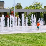 Kids splashing around the water fountain in front of the Cupertino library.