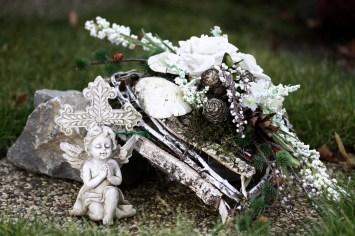 Engel neben Trauergebinde aus Birkenrinde weißen Rosen und Tannenzapfen