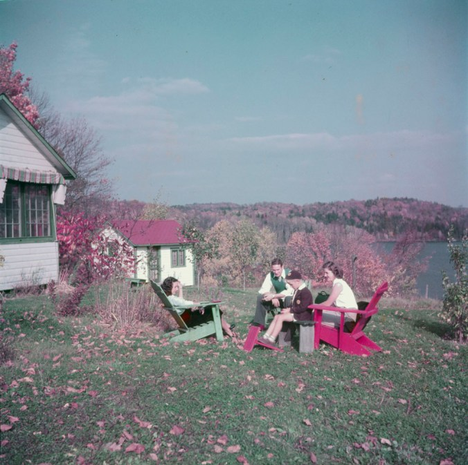 One man, two women and a young boy seated outdoors on an autumn day at a summer cottage on the Gatineau River, Quebec, October 1950, Gar Lunney, Library and Archives Canada, e010948948. CC BY 2.0
