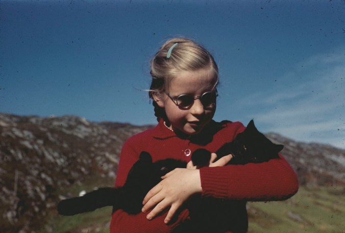 A young girl in a red sweater holding a black cat (1953-1964). Rosemary Gilliat Eaton. Library and Archives Canada, e010980903. CC BY 2.0