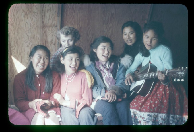 A group of six Inuit girls singing, one of them playing the guitar.
