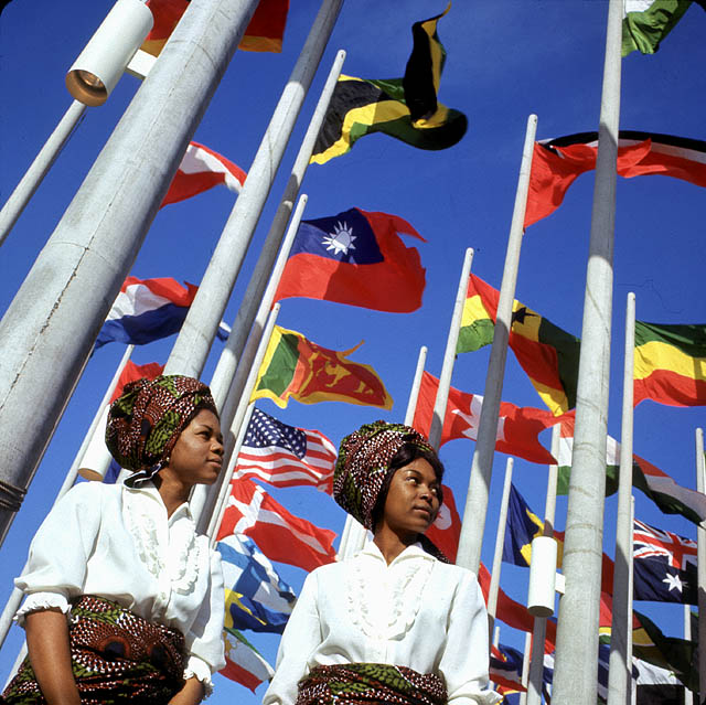 Two young women in front of flags at Place des Nations, Expo 67, on opening day.
