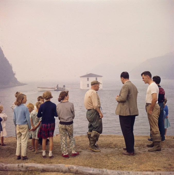 A house being floated from Silver Fox Island, Bonavista Bay, to Dover, Newfoundland. A crowd of bystanders watch as it floats off into the distance.