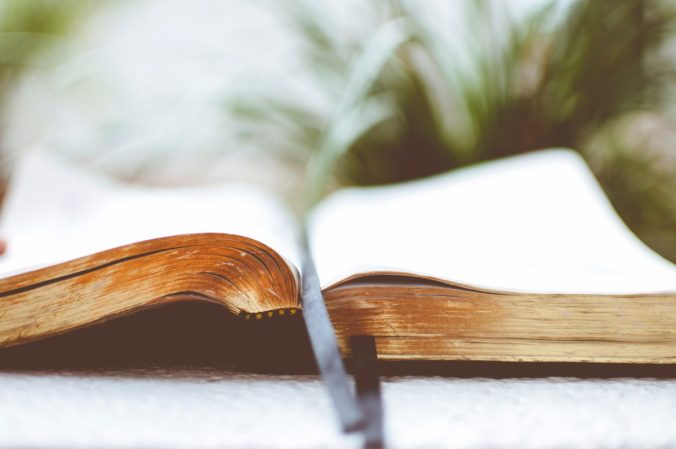 Photo of an open book with gilded pages and a grey ribbon book marker. Photo Credit Ben white Photography