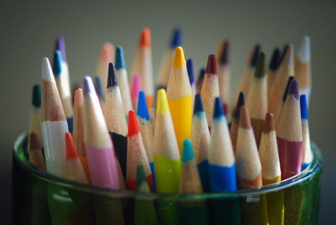 A green glass cup is filled with colouring pencils in a variety of colours encompassing the rainbow. The pencil tips are slightly blunted, and the pencil look well-used.