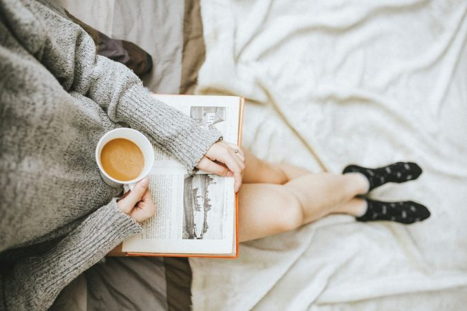 This image is of a woman sitting in bed. She is wearing a cozy grey sweater and socks, and she is holding a cup of coffee or tea with milk. In her hands is an old book with text and illustrations in black and white. The photograph was taken from above, showing the woman from the chest down.