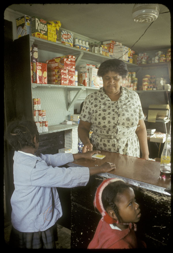 This image shows a Black woman who is presumably Matilda Newman, serving two little girls at a store counter. Newman is wearing a beige flowered shirt-dress. The little girl on the left is hearing a light blue jacket and grey skirt, and the little girl on the right is wearing a red jacket and knitted hat. In the background, there are shelves filled with grocery goods in 1960s packaging.