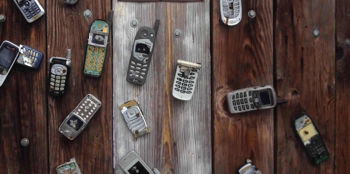 Broken phones on a wooden table.
