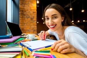 menina-sorrindo-feliz-estudando-estudante-lapis-colorido-