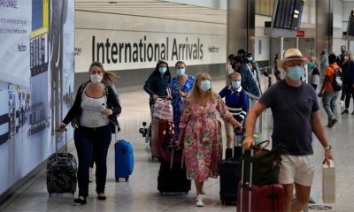 Travellers arrive at Terminal 5 of Heathrow Airport in London