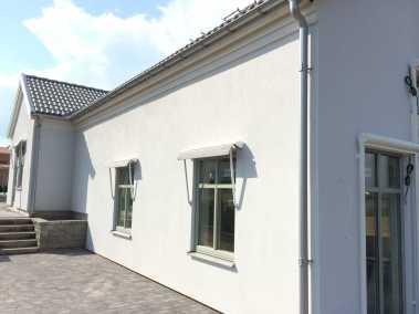 Vit fönstermarkis Java på putsat vitt hus