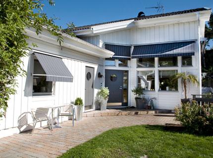 Effektivt skydd mot solen tack vare svarta snygga markiser på vitt hus.