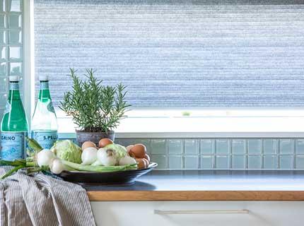 Dubbelveckade plisségardiner i fönster som solskydd