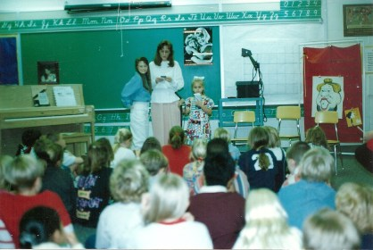 Lindsay, as a first-grader, giving a presentation to her elementary school about Down syndrome alongside her sister Leah and her mom.