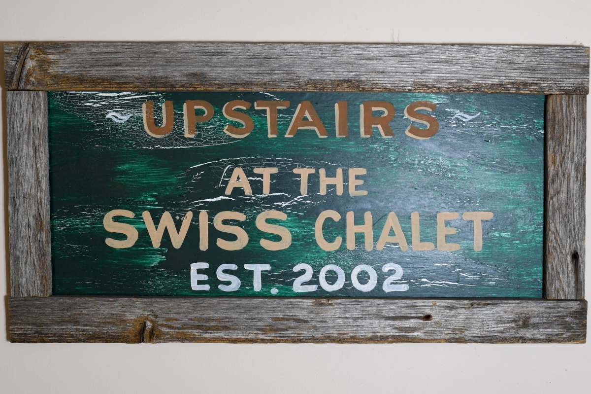 Upstairs at the Swiss Chalet Sign