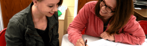two female students are looking at a notebook and laughing.
