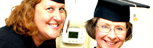 two women in graduation mortarboards, smiling.