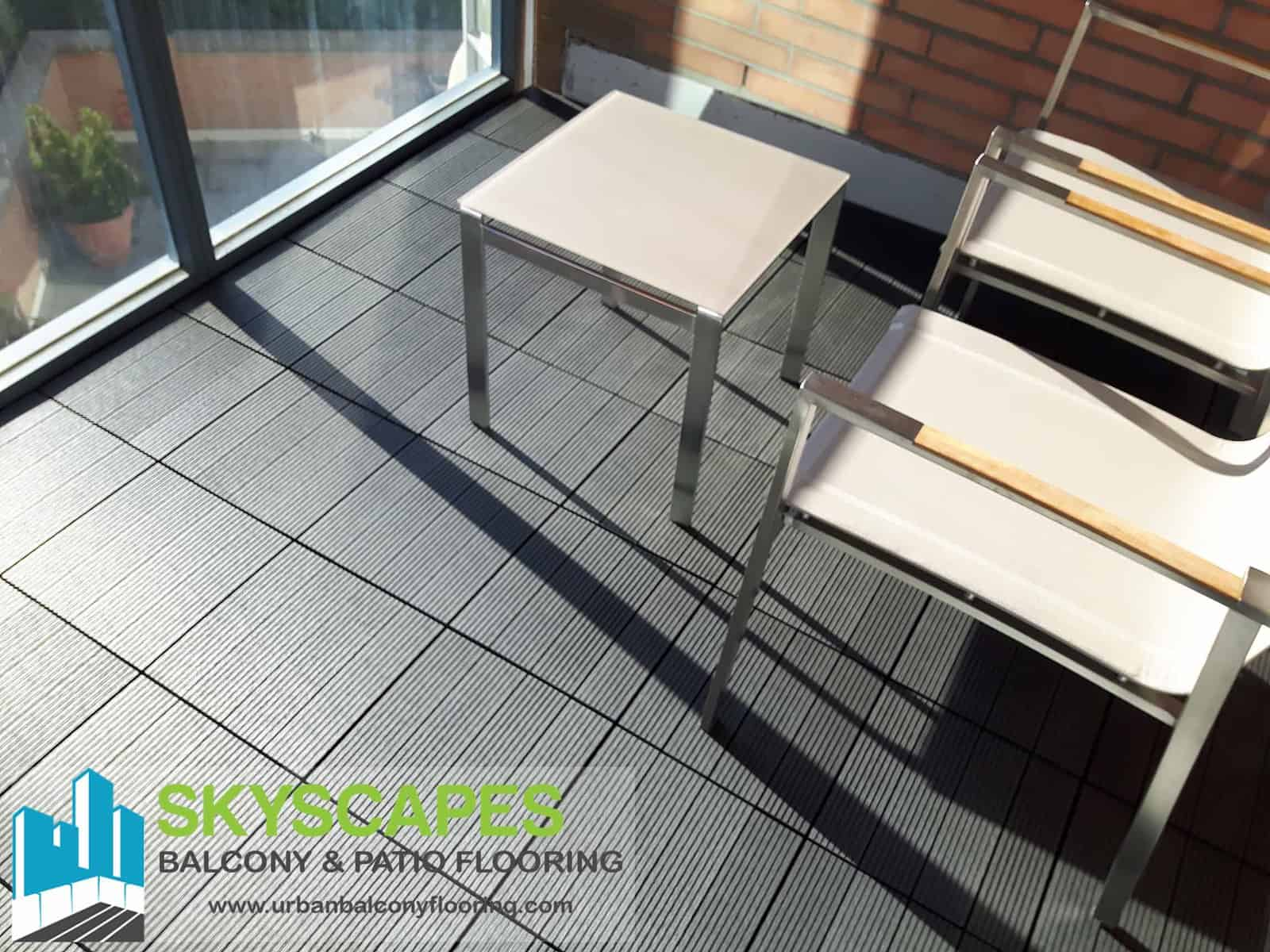 Charcoal, 4-slat, ridged WPC Tile seen on balcony floor with nice modern furniture. Measures 1 by 1 feet. Skyscapes green and blue logo at bottom-left of image.