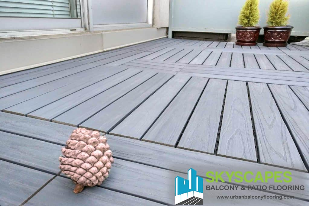 Grey, 4-slat 2x1 foot WPC tiles on balcony floor. Skyscapes green and blue logo at bottom-right of image.