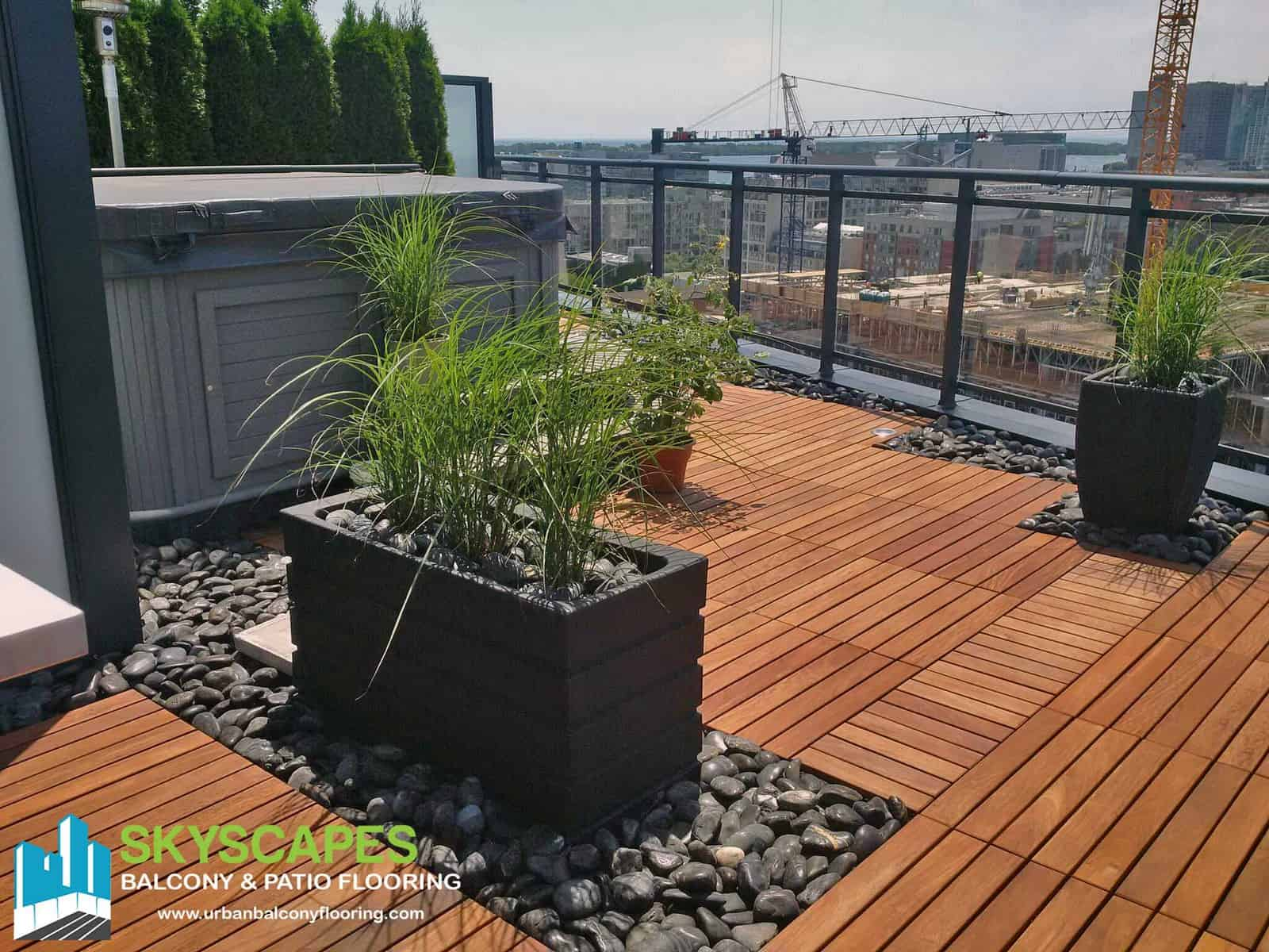 Gorgeous rooftop terrace with Ipe structural wood tiles and dark grey polished rock gardens. Skyscapes green and blue logo at bottom-left of image.