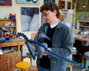 Joan with a dragon she felted out of wool from her goats.  He will soon star in a movie she will make with her students.