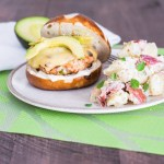 turkey burger topped with melted swiss and avocado slices with a side of red-skinned potato salad