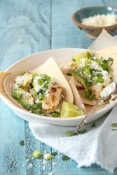 Fish tacos topped with with cilantro, green onions and yogurt sauce