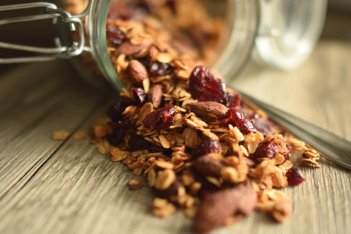 Granola with dried cranberries spilled out of a glass jar