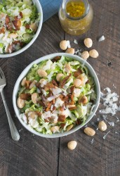Two bowls of shaved brussels sprout salad with a carafe of dressing, shot from overhead