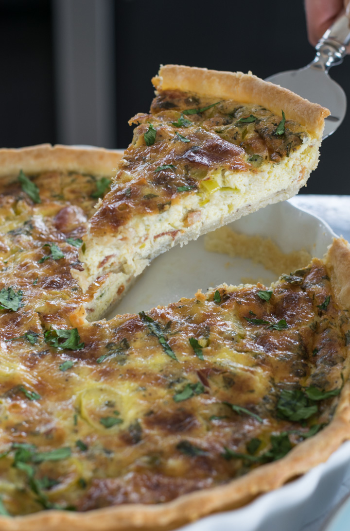 A slice of leek and pancetta quiche lifted out of the pan on a silver serving knife