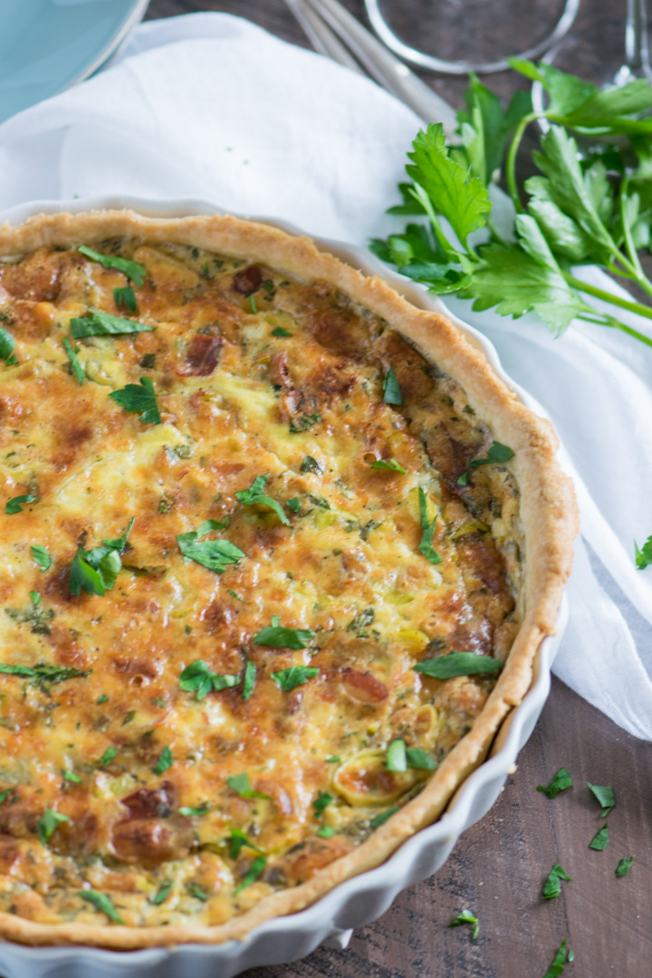 Close up image of leek and pancetta quiche in a quiche pan