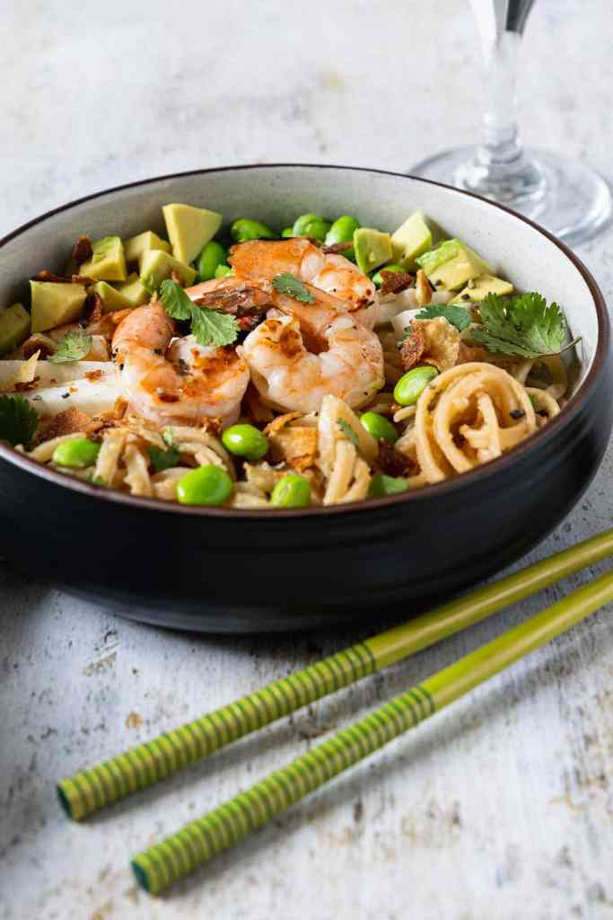 Low round bowl filled with grilled shrimp, edamame, avocado and udon noodles