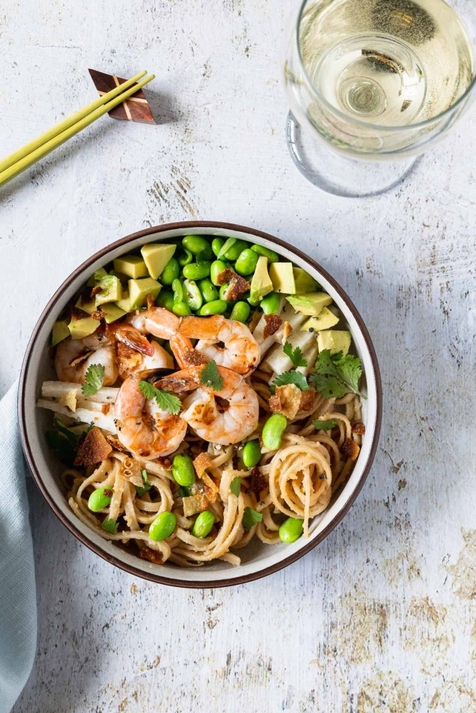 Overhead shot of grilled shrimp, edamame and avocado on top of udon noodles