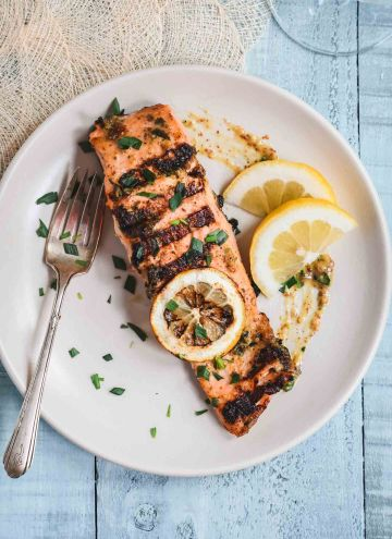 Grilled salmon filet topped with a grill lemon slice