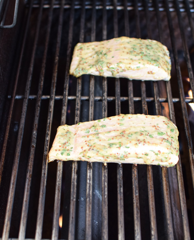 Salmon filets on the grill brushed with mustard sauce