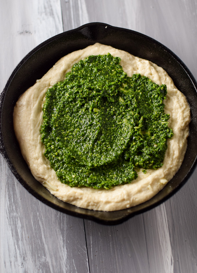 Pizza dough in mini skillet spread with kale pesto