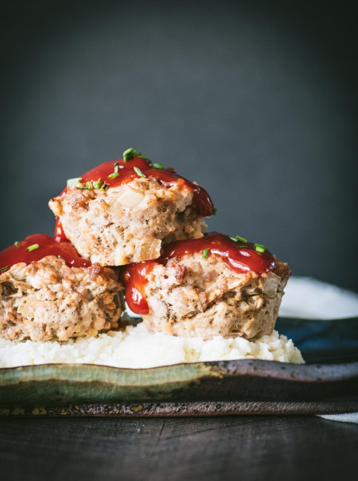 Three turkey meatloaf muffins on mashed potatoes