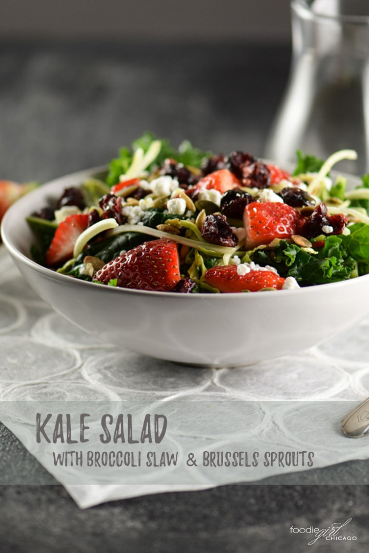 Kale salad topped with brussels sprouts, broccoli slaw and strawberries
