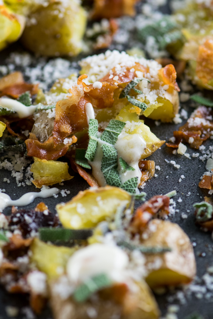 Close up of one smashed potato topped with sage and crispy pancetta