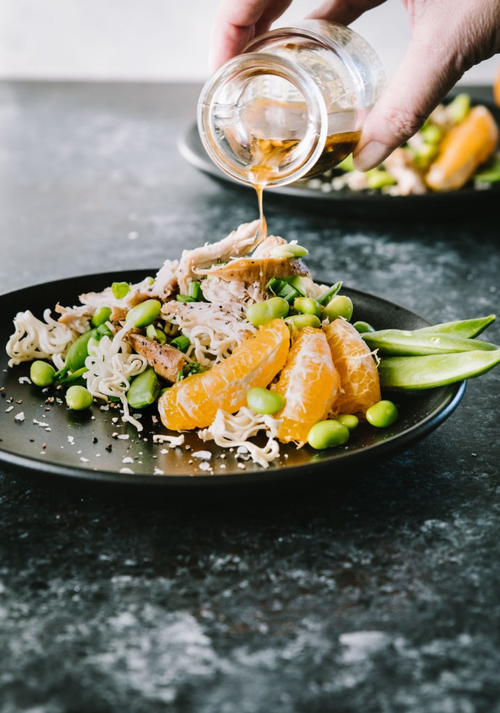 Dressing being poured over Asian Chicken Salad on a black matte plate